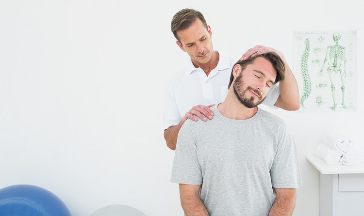 A patient is having his neck adjusted by a chiropractor